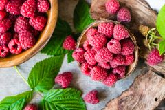 Raspberry in a bowl and in a plate, berries and leaves. On a shabby wooden table. Top view Royalty Free Stock Image