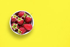 Raspberry in bowl on table. Raspberry in bowl on yellow table Stock Photo