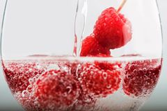 Raspberry with bubbles in glass with pouring water. Closeup Stock Photos