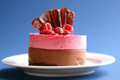 Raspberry cake. Raspberry and chocolate mousse on a blue background Royalty Free Stock Photos