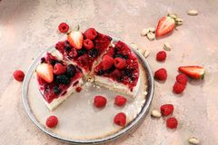 Raspberry cake and many fresh raspberries. Fresh spring cream cake with blackberries, blueberries and raspberries Royalty Free Stock Photo