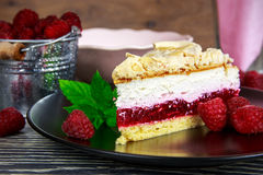 Raspberry cake. With meringue top arranged on a wooden table Royalty Free Stock Photography