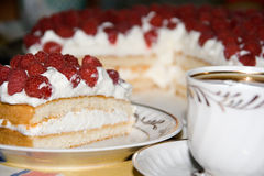 Raspberry cake and tea. Slice of layered cake topped with raspberries, a cup of tea; the rest of the cake in the background Stock Images