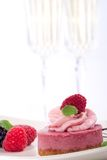 Raspberry cheesecake. Delicious raspberry cheesecake served with fresh raspberries, blackberries, mint and chocolate syrup. Two glasses of champagne out of focus Stock Images