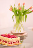 Raspberry cheesecake and vase of tulips Stock Photo