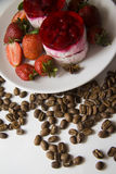 Raspberry cheesecakes on plate with coffee beans background Stock Image