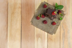 Raspberry and chocolate pieces. Enjoyment. Fresh ripe raspberries with leaves and slices of chocolate on wooden background. Top view. The selected focus Stock Photo