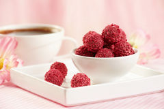 Raspberry chocolate truffles. In white bowl on pink background royalty free stock image