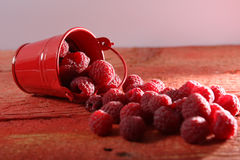 Raspberry close-up. Raspberries  and a small bucket on a wooden background Royalty Free Stock Photos