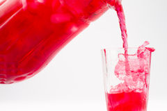 Raspberry cold drink poured into a glass. Raspberry diluted concentrate cold drink poured from a glass container into a glass filled with ice Stock Image