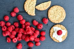 Raspberry and cookies. Healthy eating, food, dieting - oat cookies with  fresh raspberry soft cheese on black slate Stock Images