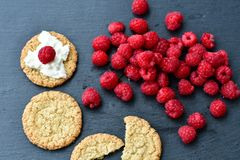 Raspberry and cookies. Healthy eating, food, dieting - oat cookies with  fresh raspberry soft cheese on black slate Royalty Free Stock Images