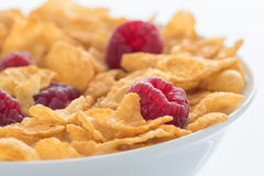 Raspberry and Cornflakes in a white Bowl. Healthy breakfast with cornflakes, raspberry and milk in a white bowl Royalty Free Stock Image