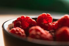 Raspberry in a cup on  blurred background of wooden planks. Raspberry in a cup on a blurred background of wooden planks Stock Photo