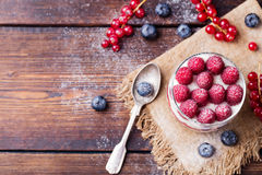 Raspberry dessert, cheesecake, mouse in a glass. Raspberry dessert, cheesecake, trifle, mouse in a glass on a wooden background.Top view Copy space Royalty Free Stock Image