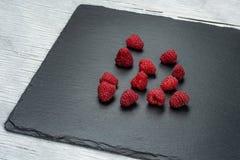 Raspberry dessert and fresh raspberries on a black wooden table  raw cake. Raspberry dessert and fresh raspberries on a black wooden table Raspberry raw cake Stock Photo
