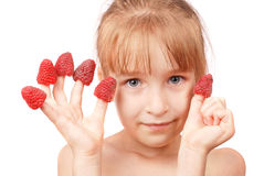 Raspberry on fingers of a little girl Royalty Free Stock Images