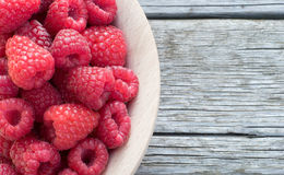 Raspberry. Fresh Organic Raspberry in wooden bowl on wooden boards. Closeup with copy space Royalty Free Stock Photo