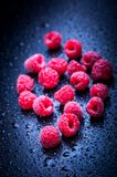Raspberry. Fresh raspberries after rain on blue Stock Photography