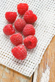 Raspberry in front of white fabric on old vintage wooden tab Royalty Free Stock Photography