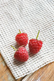 Raspberry in front of white fabric on old vintage wooden tab Stock Image