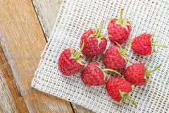 Raspberry in front of white fabric on old vintage wooden tabl Royalty Free Stock Photos