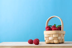 Raspberry Fruit Basket on Blue Background Stock Photo