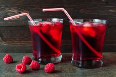 Raspberry fruit drinks with bendy straws over a dark background Royalty Free Stock Photos