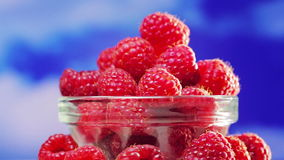 Raspberry fruit heap rotating on  blue stock footage