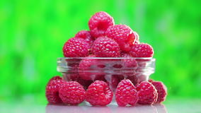 Raspberry fruit heap rotating on green stock video