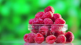 Raspberry fruit heap rotating on green stock footage