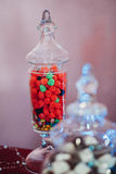Raspberry fruit jelly beans in a flask of glass. Fruity red raspberry jelly beans in a flask of glass, full glass, beautiful delicious dessert, decor Royalty Free Stock Photo
