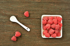Raspberry. Fruit on wood background. Forest fruit in white idaeus and spoon. Delicious fresh berries Stock Image