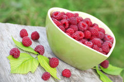 Raspberry in green bowl. On wooden background Stock Photos