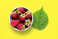 Raspberry and green leaf. On yellow table Stock Images