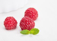 Raspberry green leaves and white bowl. Closeup Stock Images