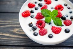 Raspberry and green mint. Fresh yoghurt with raspberry and green mint on wooden table. sweet dessert food Royalty Free Stock Image