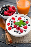 Raspberry and green mint. Fresh yoghurt with raspberry and green mint on wooden table. sweet dessert food Stock Photography