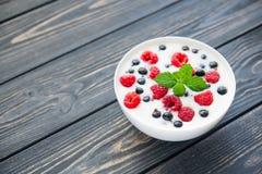 Raspberry and green mint. Fresh yogurt with raspberry and green mint on wooden table. sweet dessert food Stock Photography