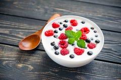 Raspberry and green mint. Fresh yogurt with raspberry and green mint on wooden table. sweet dessert food Stock Photo