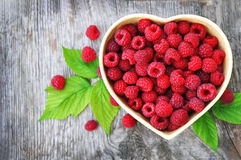 Raspberry and heart. Raspberry in plate in form of heart on wooden table Royalty Free Stock Photo