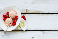 Raspberry ice-cream. Ceramic bowl of pink melting raspberry ice-cream with fresh berries and white chocolate on wooden background, top view, copy space Stock Photo