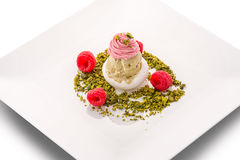 Raspberry ice cream with pistachios and fresh raspberries on white plate, exclusive summer dessert, patisserie.  Royalty Free Stock Photo