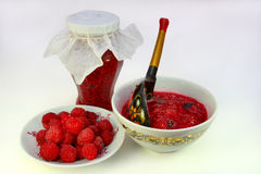 The raspberry jam. Fresh raspberry on a saucer, crimson jam in Pialat and in bank on a light  background Royalty Free Stock Photos