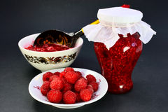 The raspberry jam. Fresh raspberry on a saucer, crimson jam in Pialat and in bank on a dark background Stock Photography