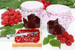 Raspberry jam. Two glasses of homemade raspberry jam with fresh fruits, toast and leaves stock image