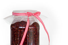 Raspberry jam. Jar of home made raspberry jam tied with a gingham ribbon Stock Image