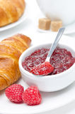 Raspberry jam, fresh croissant and cup of coffee. Close-up Stock Photo