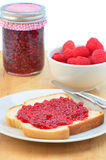 Raspberry jam. Fresh home made raspberry jam with slice of bread and jam and fresh raspberries, vertical composition Stock Image