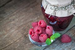 Raspberry jam with fresh raspberries. On the old wooden background Royalty Free Stock Photography